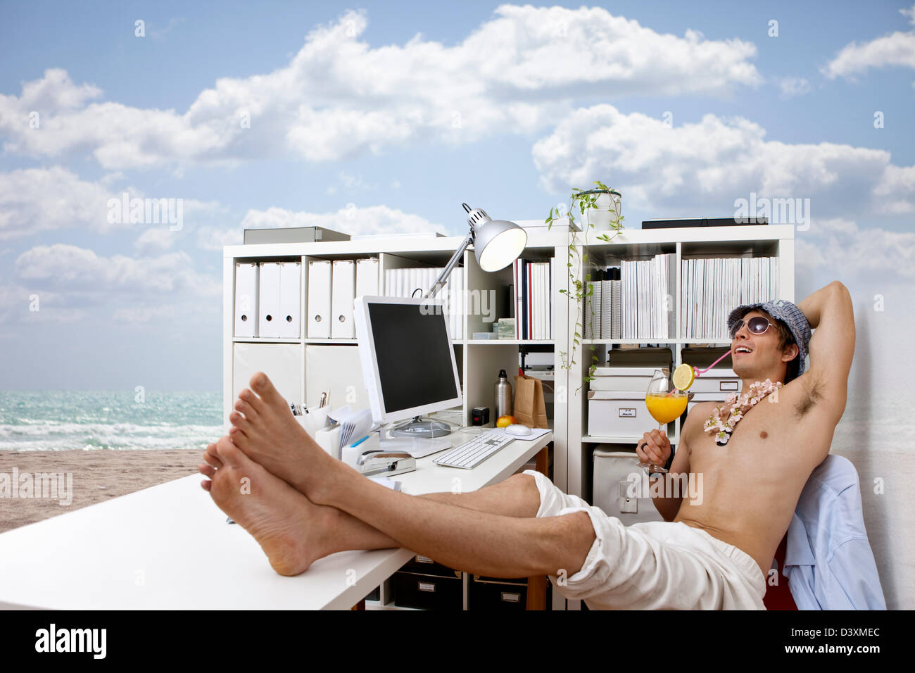 young man at work daydreaming about beach, cocktails, easy life - Stock Image