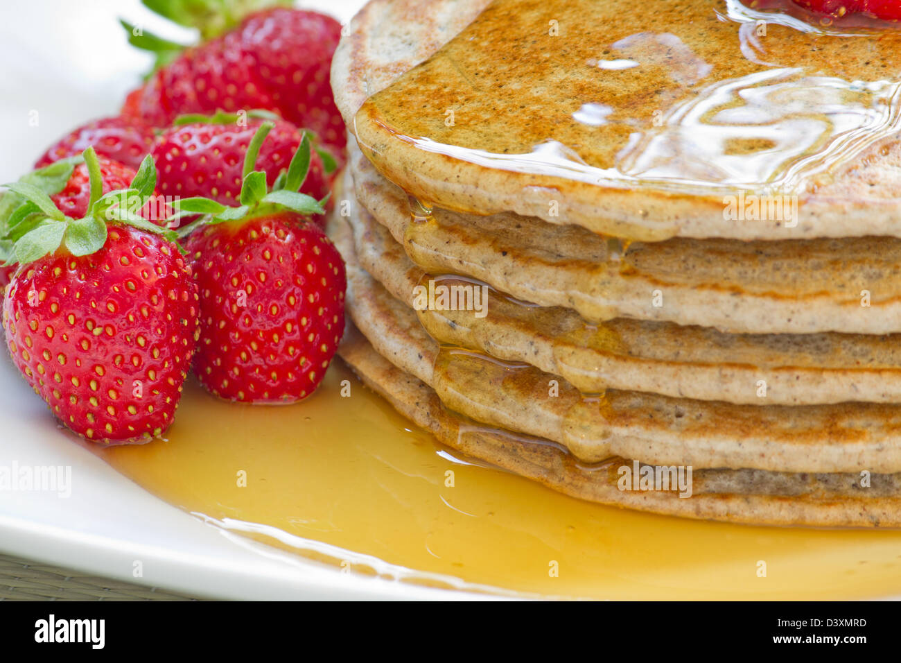 Pancakes closeup with a strawberry and maple syrup garnish. - Stock Image