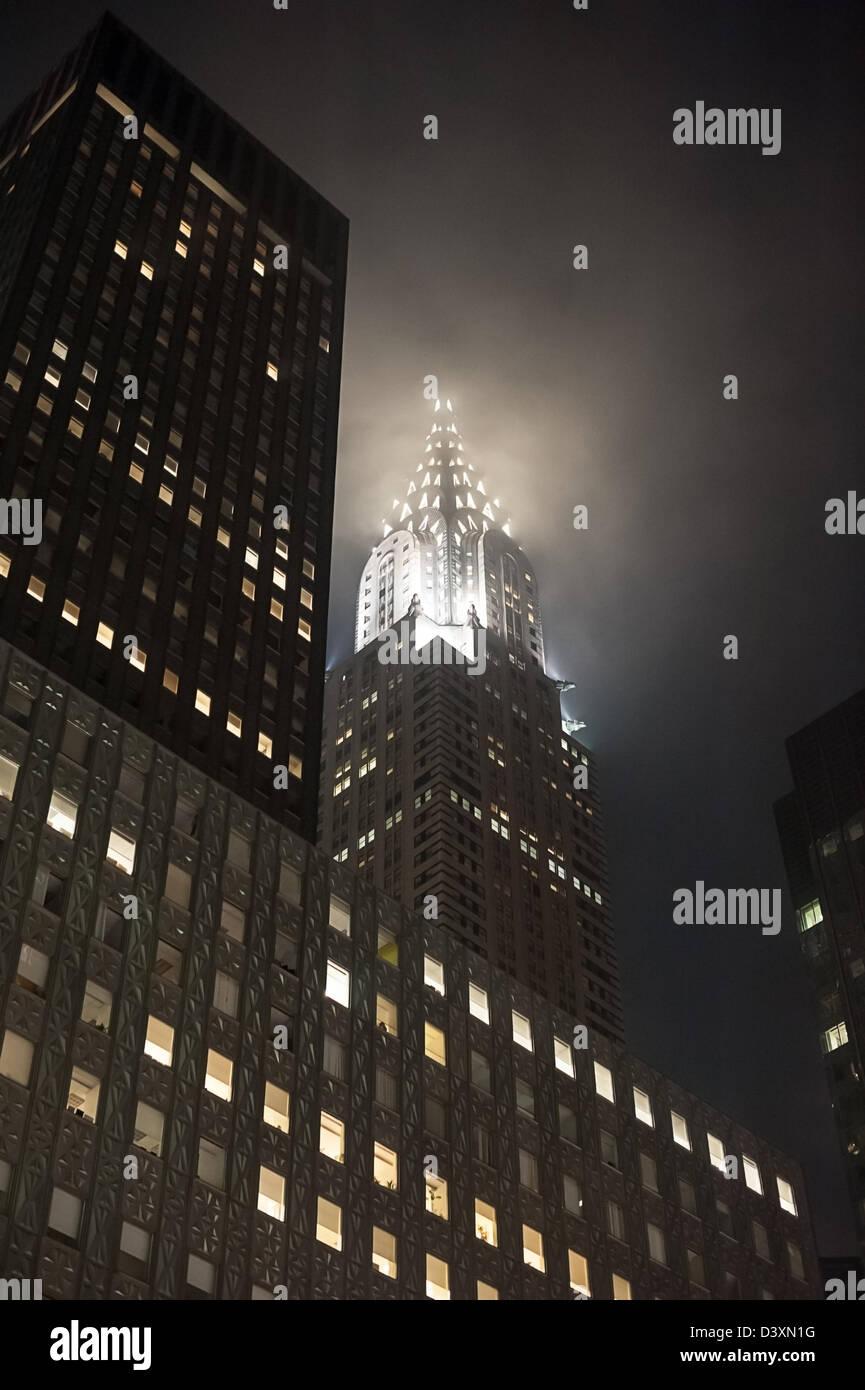 The eerie sight of New York's Chrysler Building shrouded in fog at night. - Stock Image
