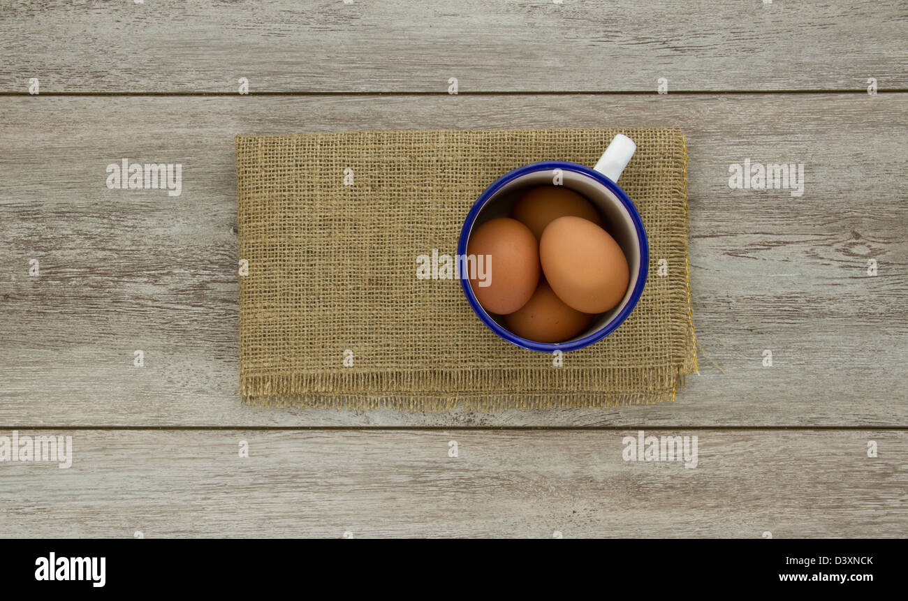 A blue and white enamel mug containing four brown chicken eggs, on burlap and weathered boards. - Stock Image