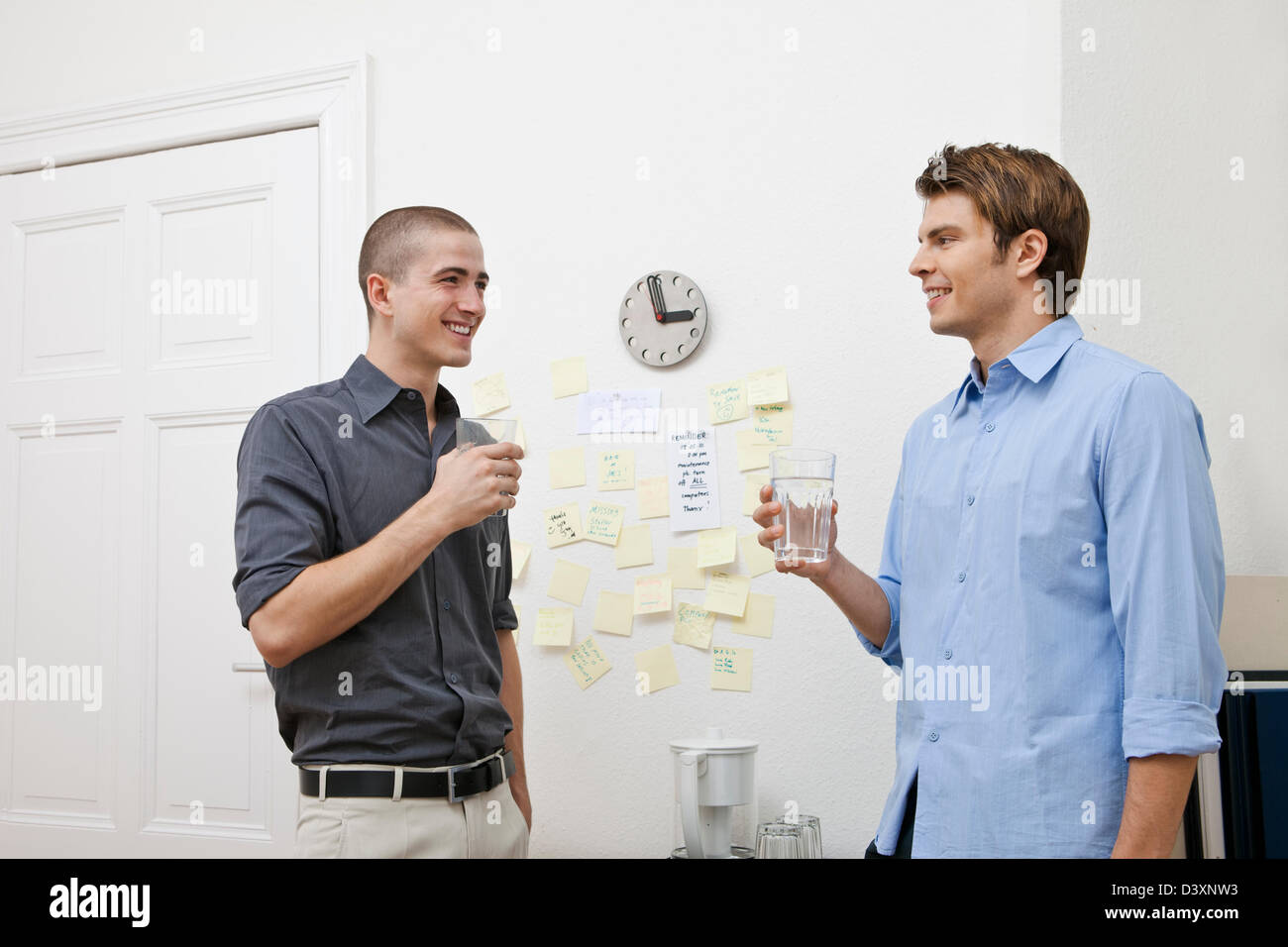 office workers chatting in the pantry while taking a break. Black Bedroom Furniture Sets. Home Design Ideas
