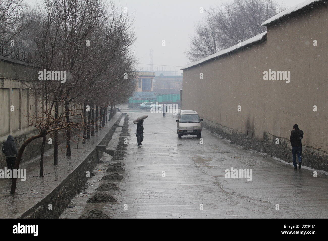 A sodden street in Kabul. Resident stoop low against a wet wind. - Stock Image