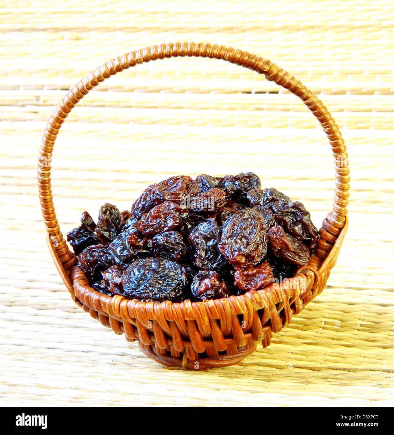 Black raisin in wicker basket on matting sunlight background - Stock Image