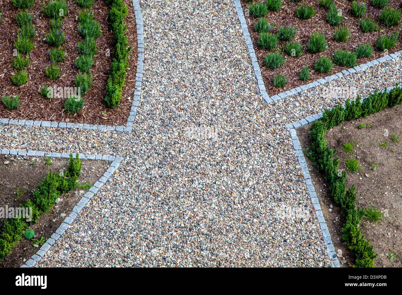 Crossroad, path with pebbles, in a garden. - Stock Image