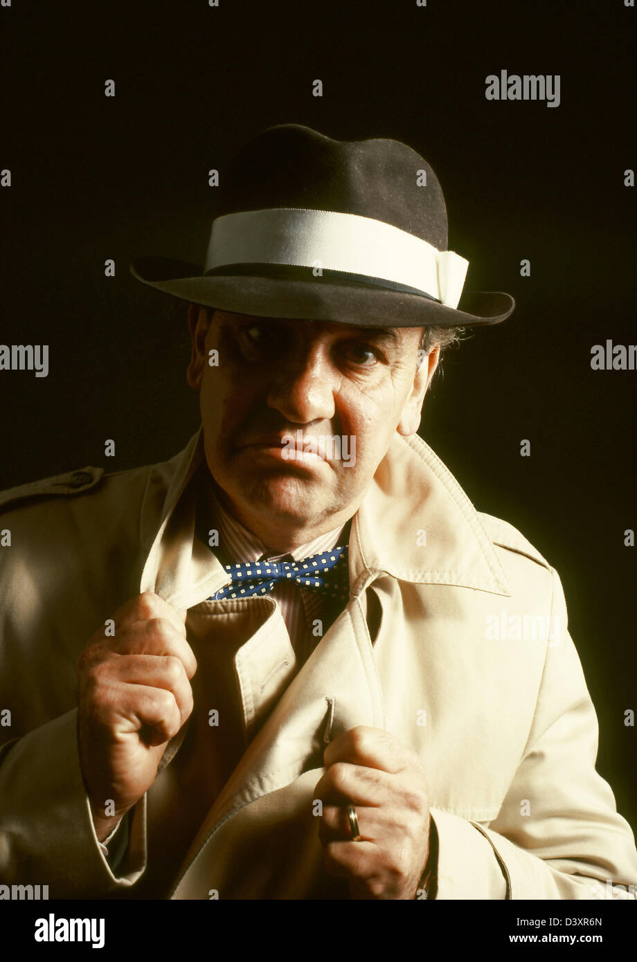 An aggressive looking man gangster dressed in trench coat and trilby hat,nasty man,dept collector, - Stock Image