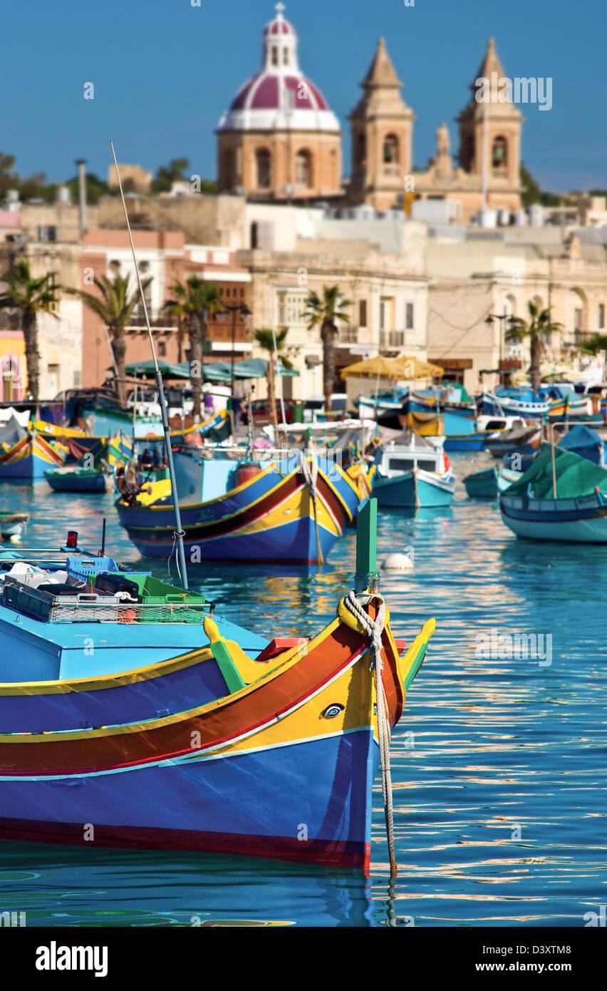 Traditional Maltese fishing boat.Parish Church,Marsaxlokk,Malta. - Stock Image