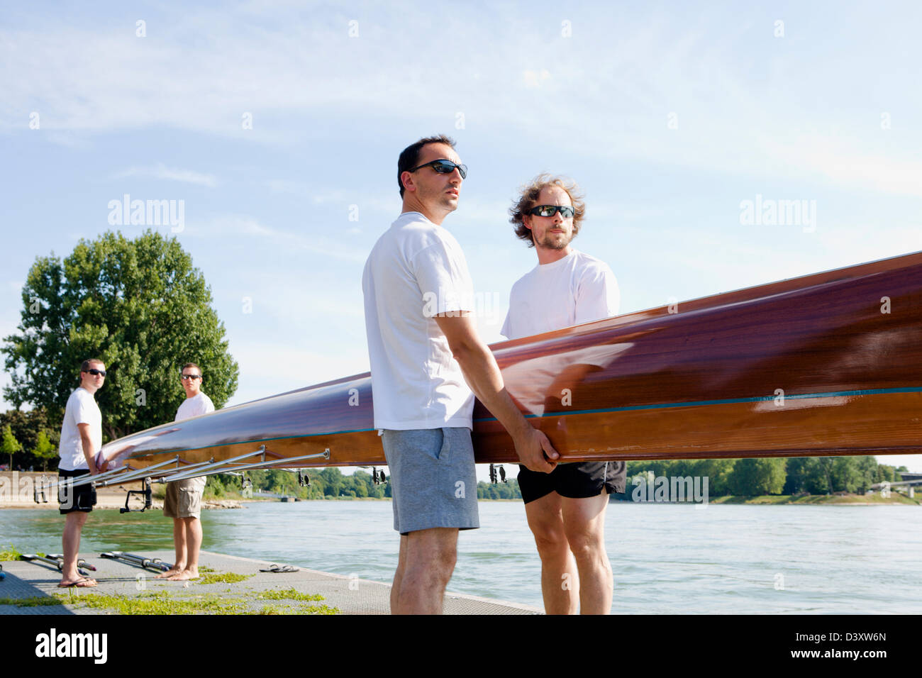 Teamwork Concept of Men Rowing Team Carrying Boat to Water - Stock Image