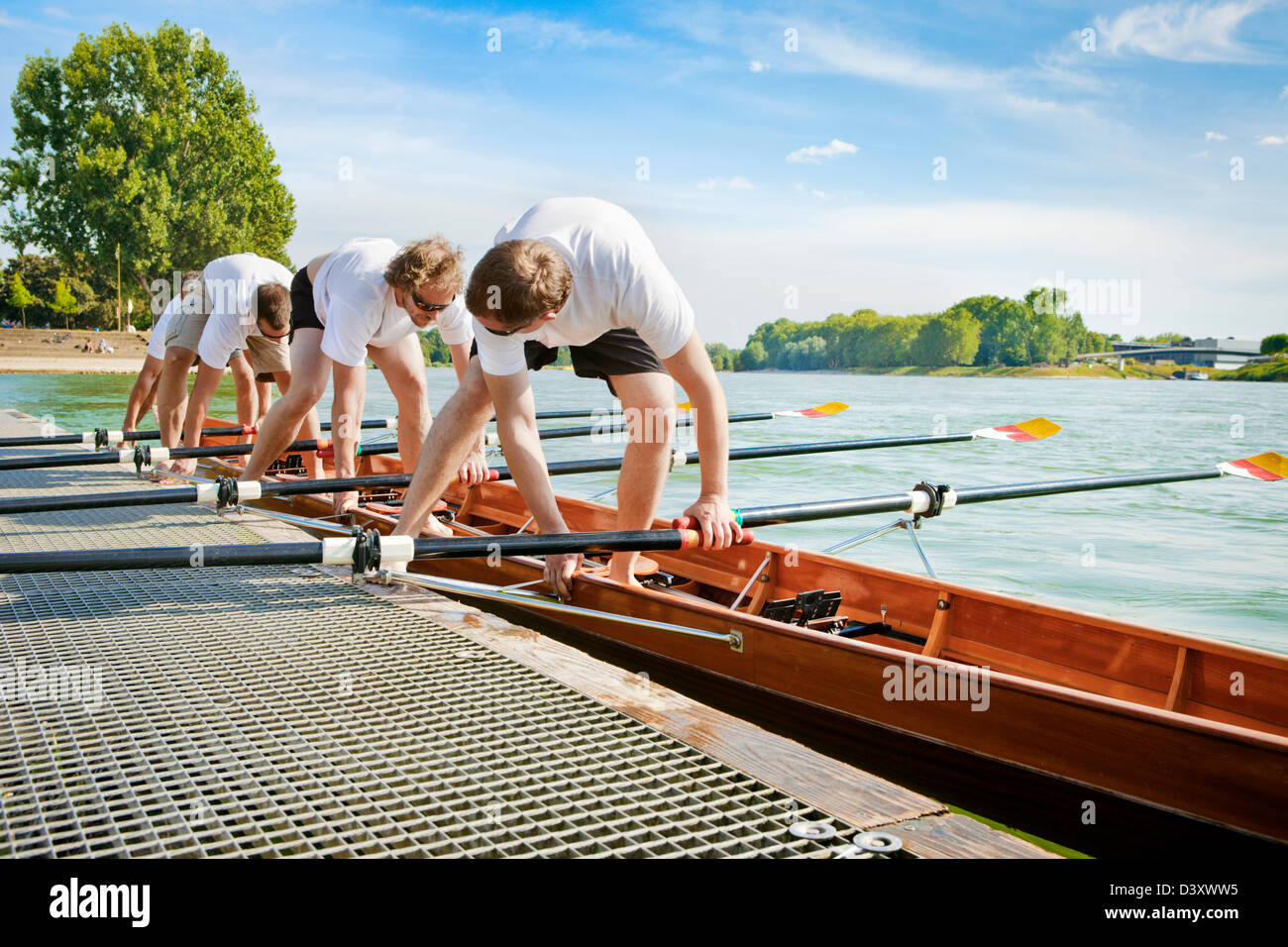Teamwork Concept of Men Rowing Team Mounting Boat in Coordination - Stock Image