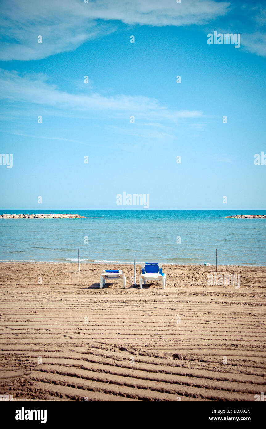 two empty sunbeds in off-season time on Larnaca beach, Cyprus - Stock Image