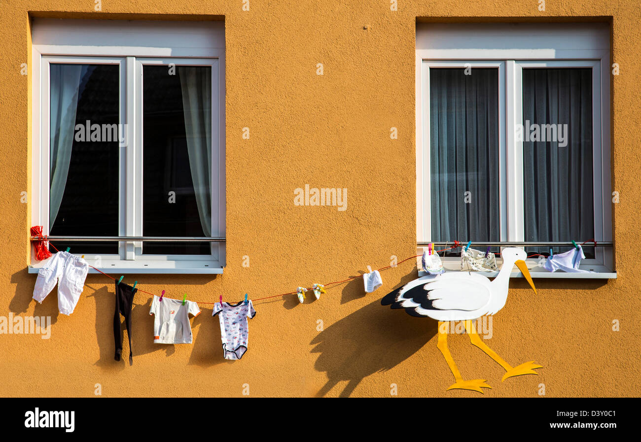 Stork and clothes hanging on a house. Customs will, from neighbors, friends hanging at the family house, when a - Stock Image