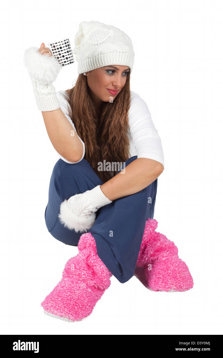 Young and attractive girl sitting and drinking coffee in cold weather with her beret in cozy clothing - Stock Image