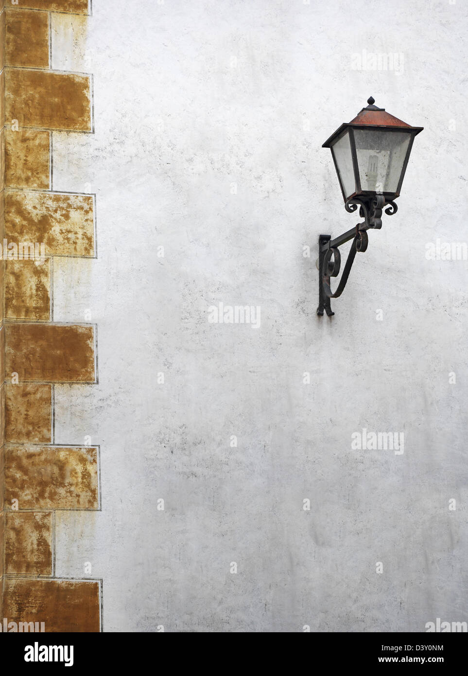 Classic street lantern with wrought iron, on the wall of the old house - Stock Image