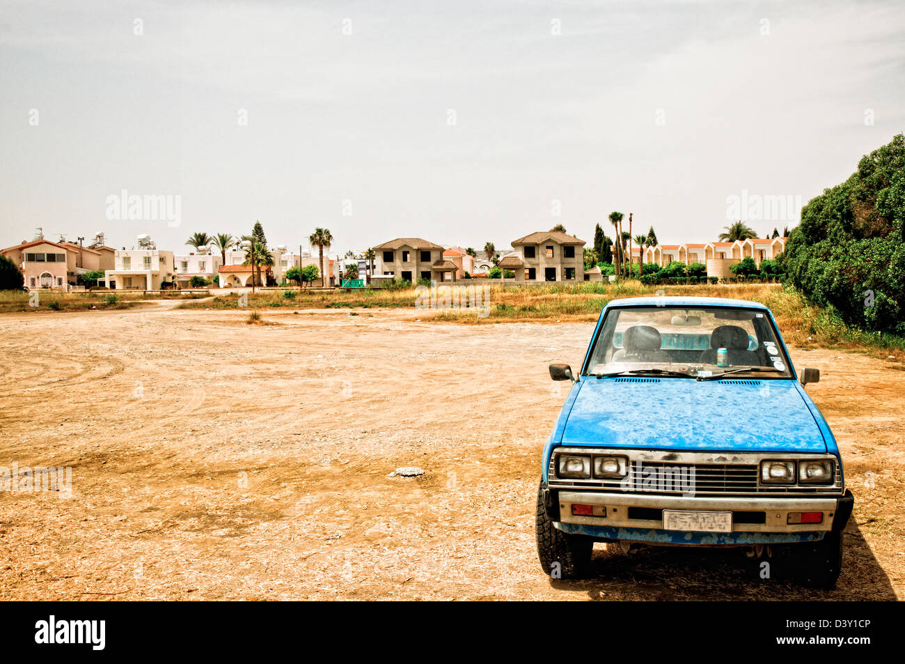 lone rusty car parked in a desolate scenery - Stock Image