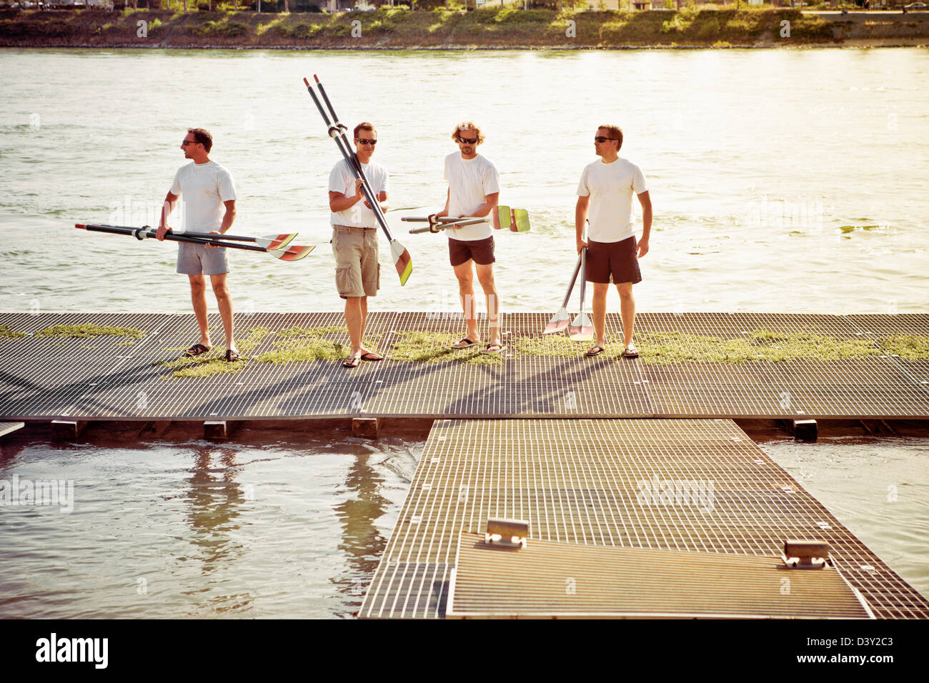 Male rowing team carrying paddles on shoulders coming in after a rowing practice - Stock Image