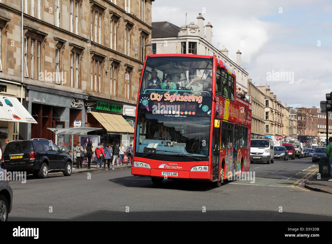 An open top tourist bus on Byres Road in the West End of Glasgow, Scotland, UK - Stock Image