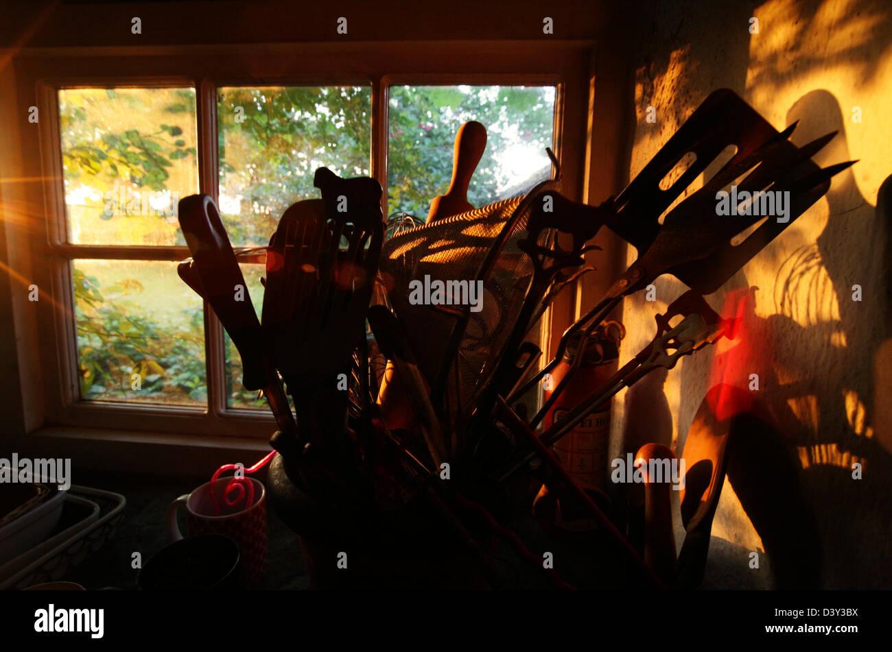 Golden sunlight through kitchen window illuminating utensils - Stock Image
