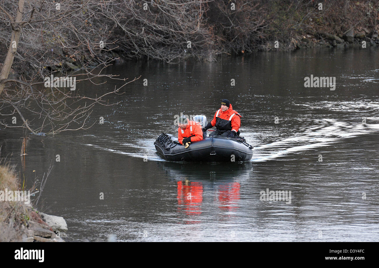 Police search for a man's body after he was hit by a train and thrown into a river. - Stock Image
