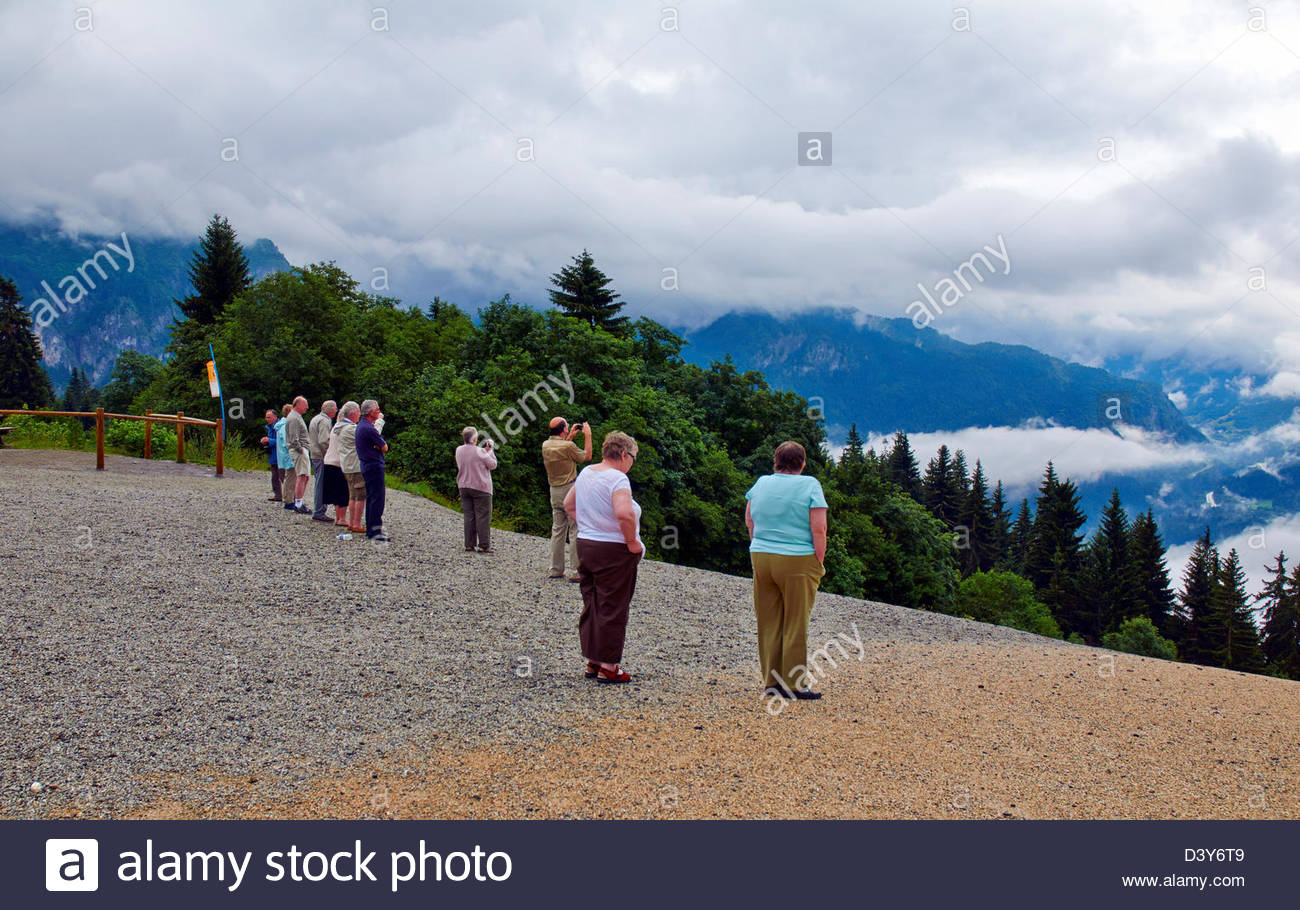 group of sightseers tourists looking at mont blanc mountain range in france - Stock Image