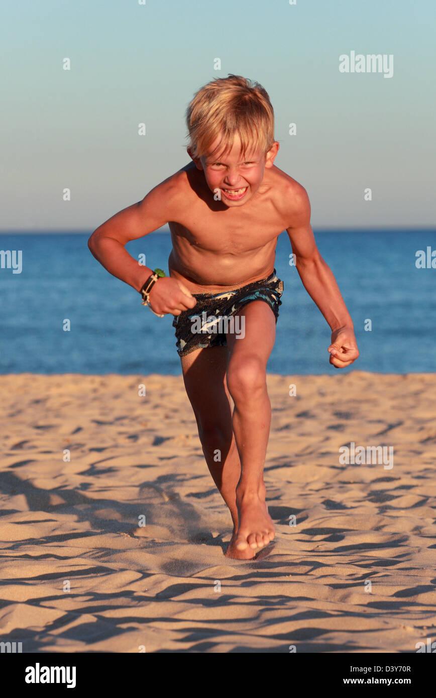 Santa Margherita di Pula, Italy, angry boy at the beach running towards the viewer - Stock Image