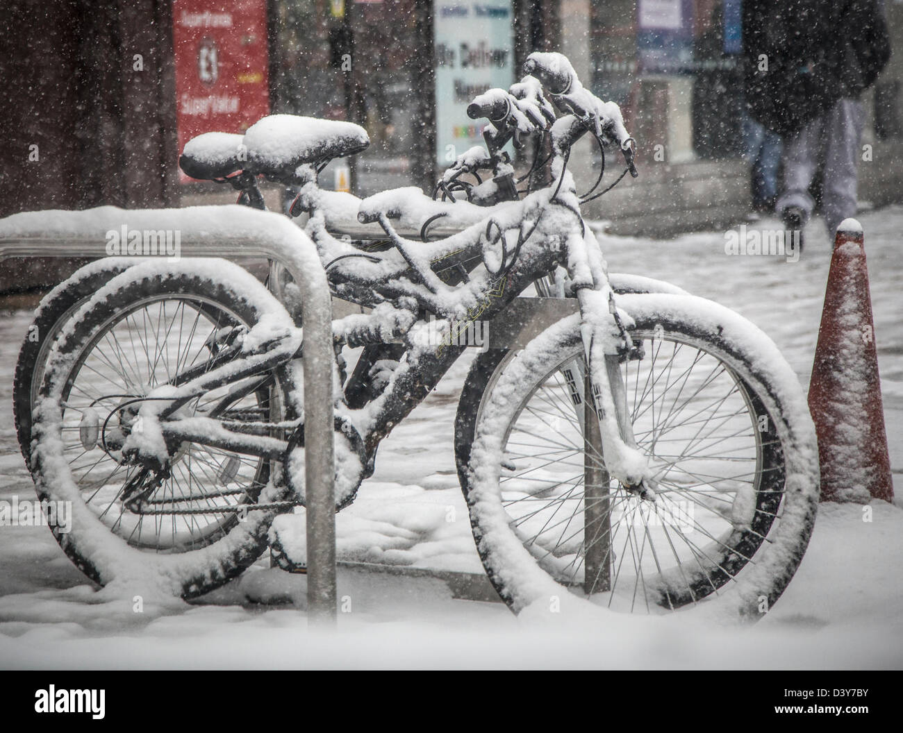 Two bicycles covered in snow await their riders after heavy snowfall hit the UK. - Stock Image