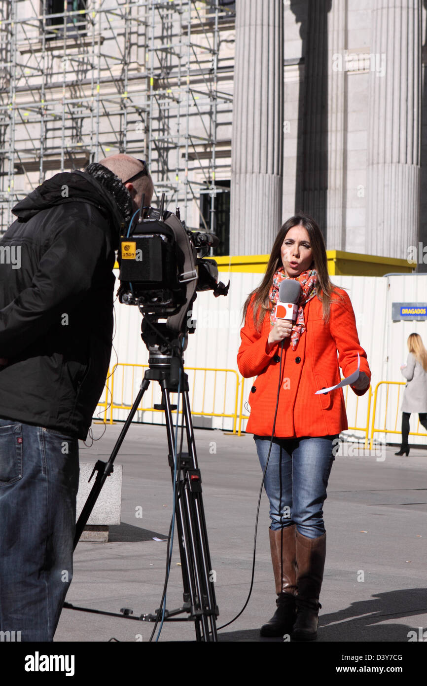 TV new reporter journalist and film crew cameraman recording in Madrid Spain - Stock Image