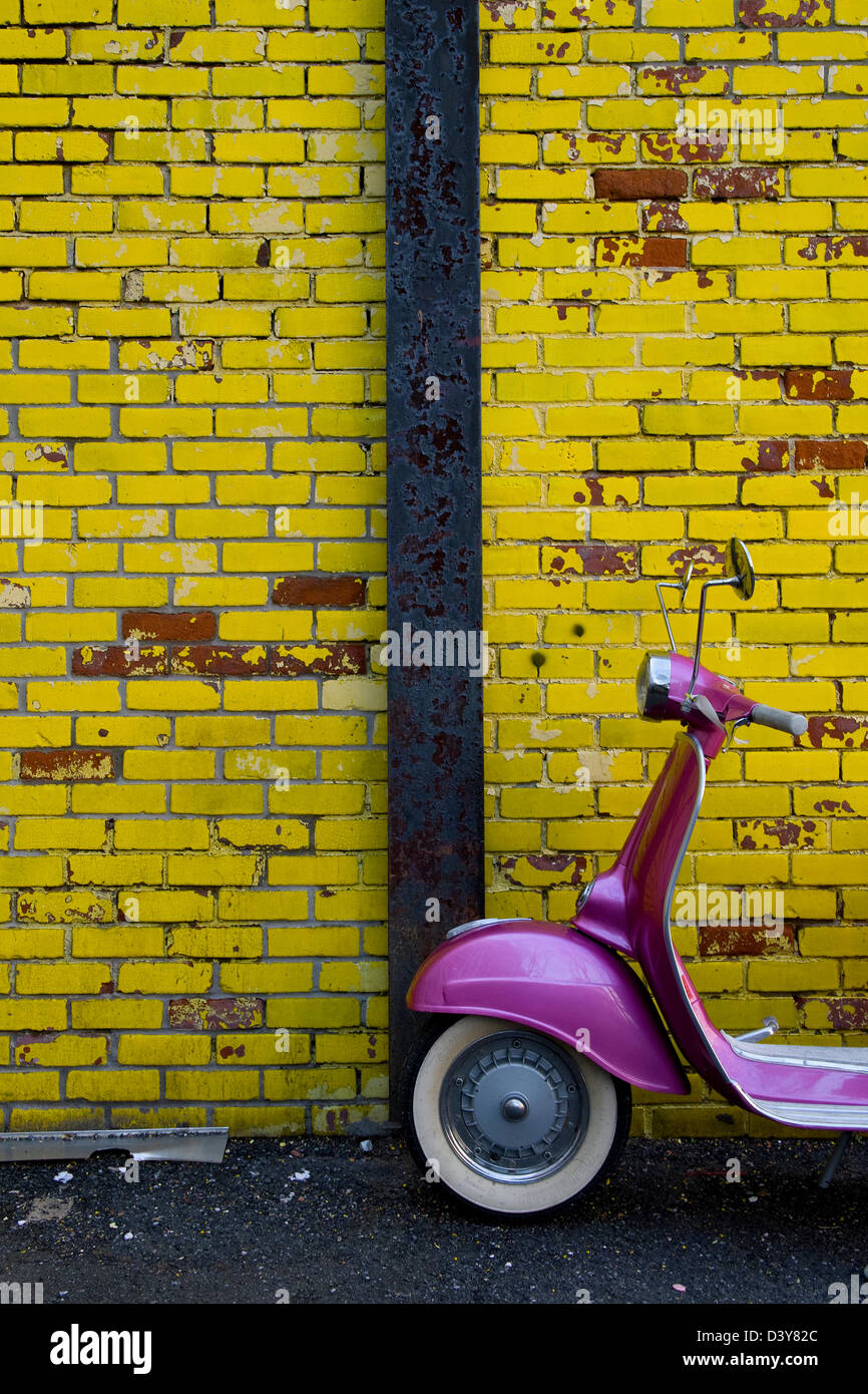 A colorful pink scooter against a yellow brick wall. - Stock Image