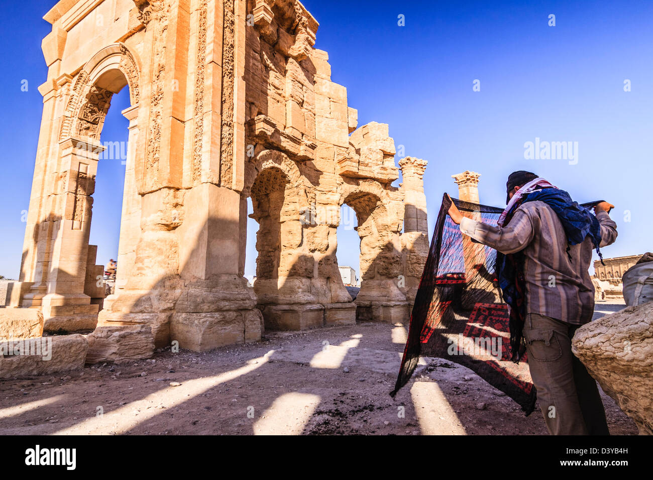 Silk souvenirs seller waiting for tourists at the Monumental Arch of Palmyra ruins. Palmyra, Syria - Stock Image