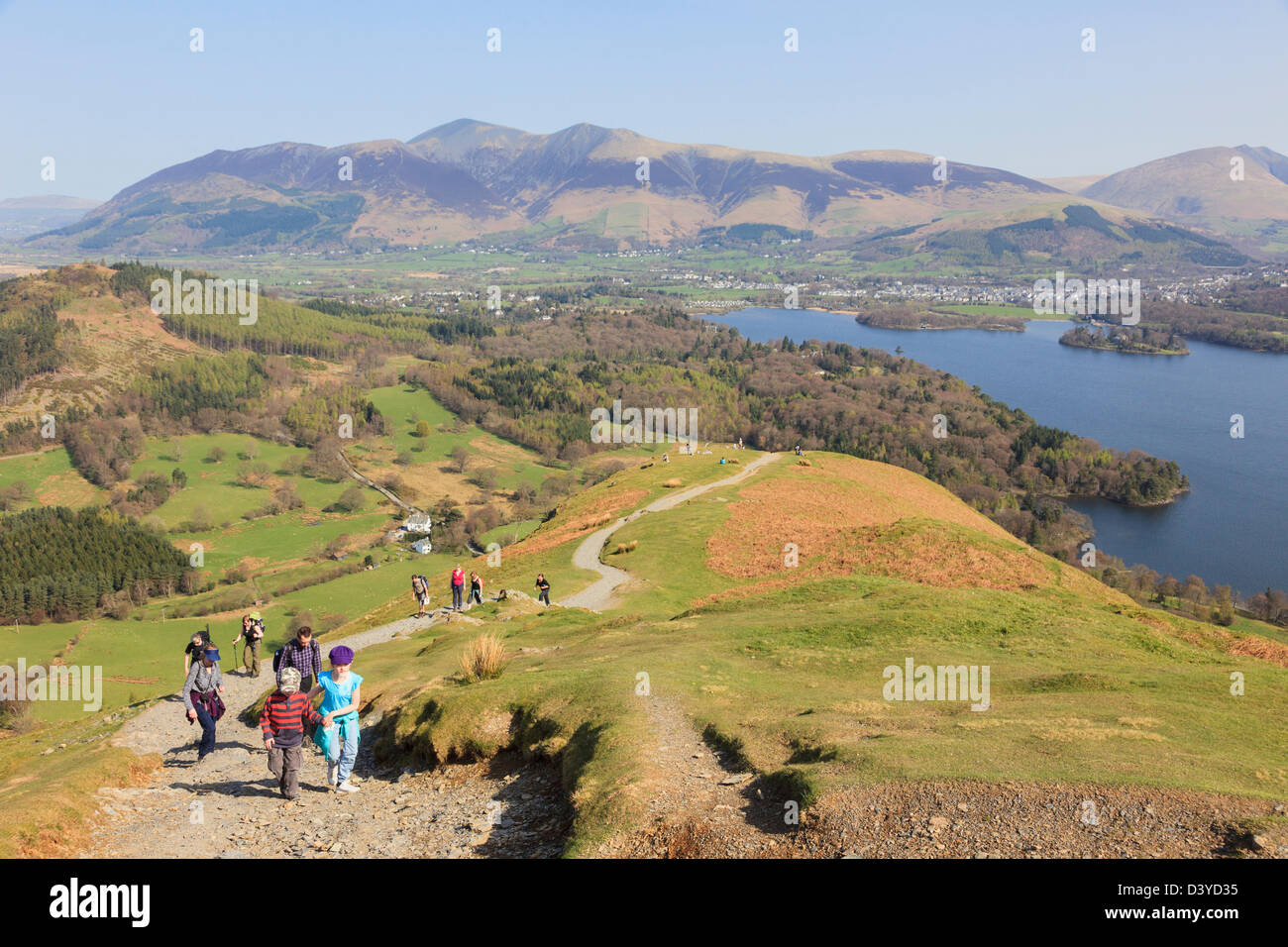 People walking on a footpath up Catbells on sunny day with view overlooking Derwent Water in northern Lakes. Borrowdale - Stock Image