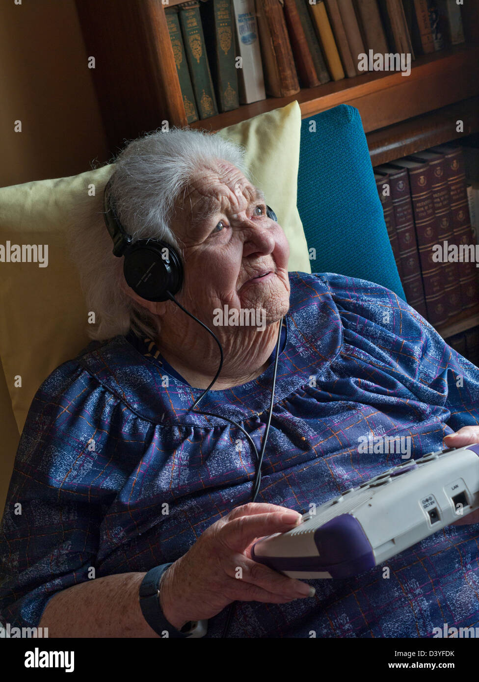 Elderly lady listening to an audio book, with a CD player designed