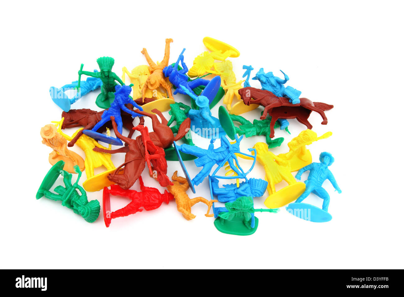 An assortment of toy cowboys and Indians in a loose pile on white background. - Stock Image