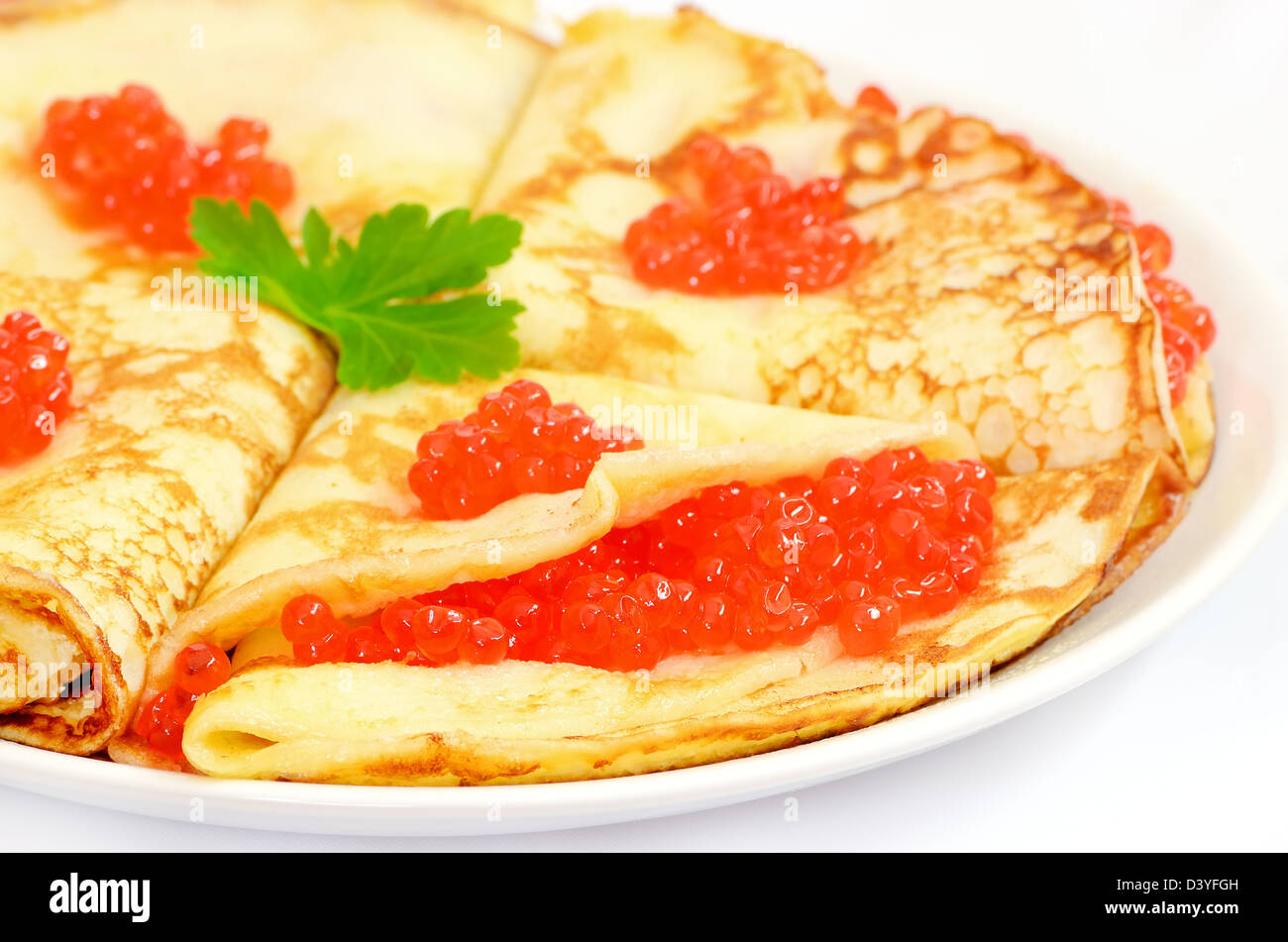 Pancakes with red caviar on a plate on white background - Stock Image