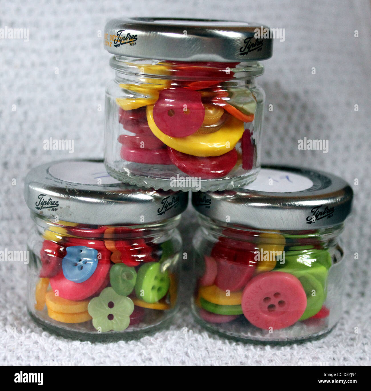 Three small glass jars stacked in a triangle, the jars containing a colorful  selection of clothes buttons. - Stock Image