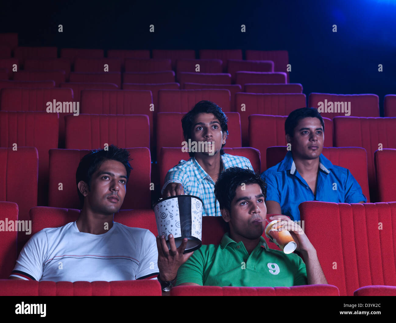 Youngsters enjoying movie with popcorns in a cinema hall Stock Photo
