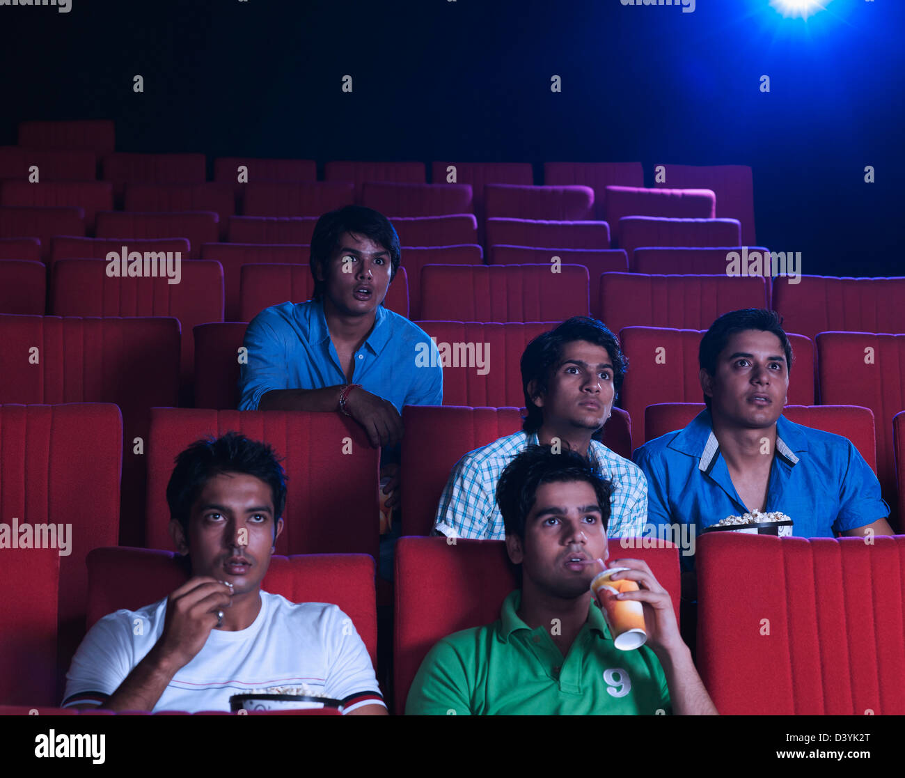 Youngsters enjoying movie in a cinema hall Stock Photo