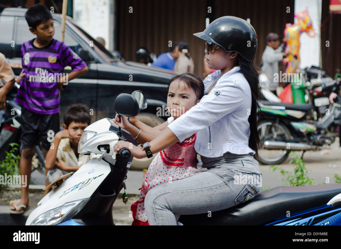 Mother and daughter on scooter in Ketapang, West Kalimantan - Stock Image