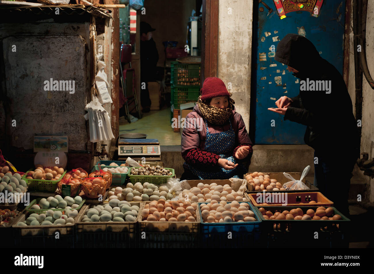 A customer purchases eggs from an elderly market vendor at Guangqi Road Market, Shanghai - Stock Image