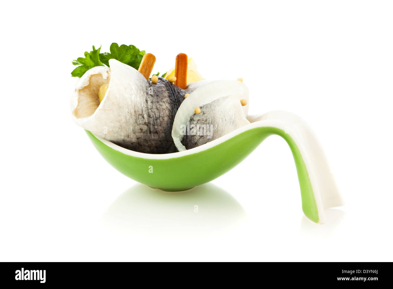 German Rollmops  - kipper wrapped around pickled cucumber - on serving spoon isolated on white background - Stock Image