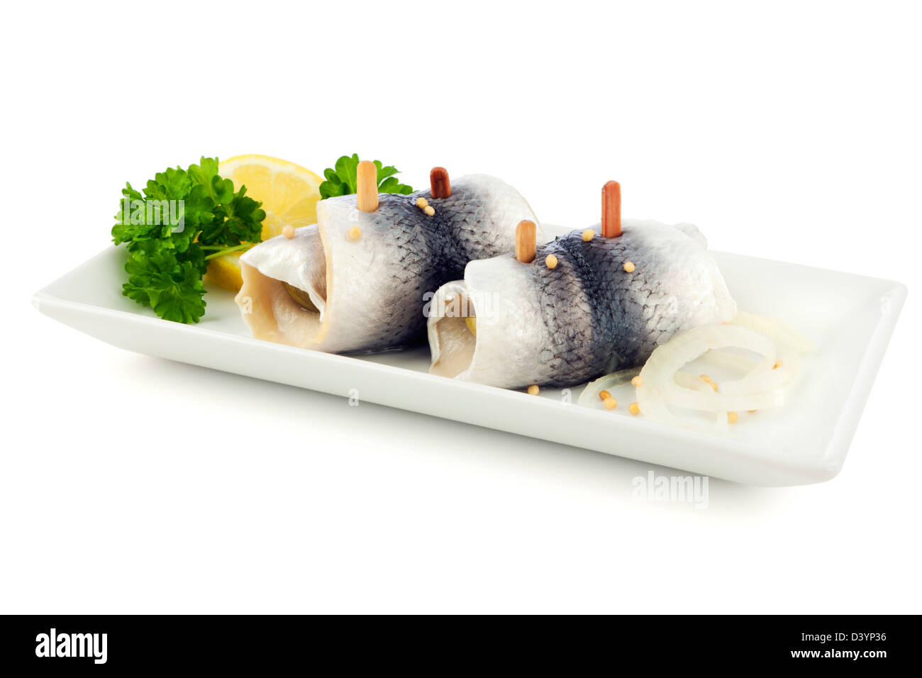 German Rollmops - kipper wrapped around pickled cucumber - on a square plate on white background - Stock Image