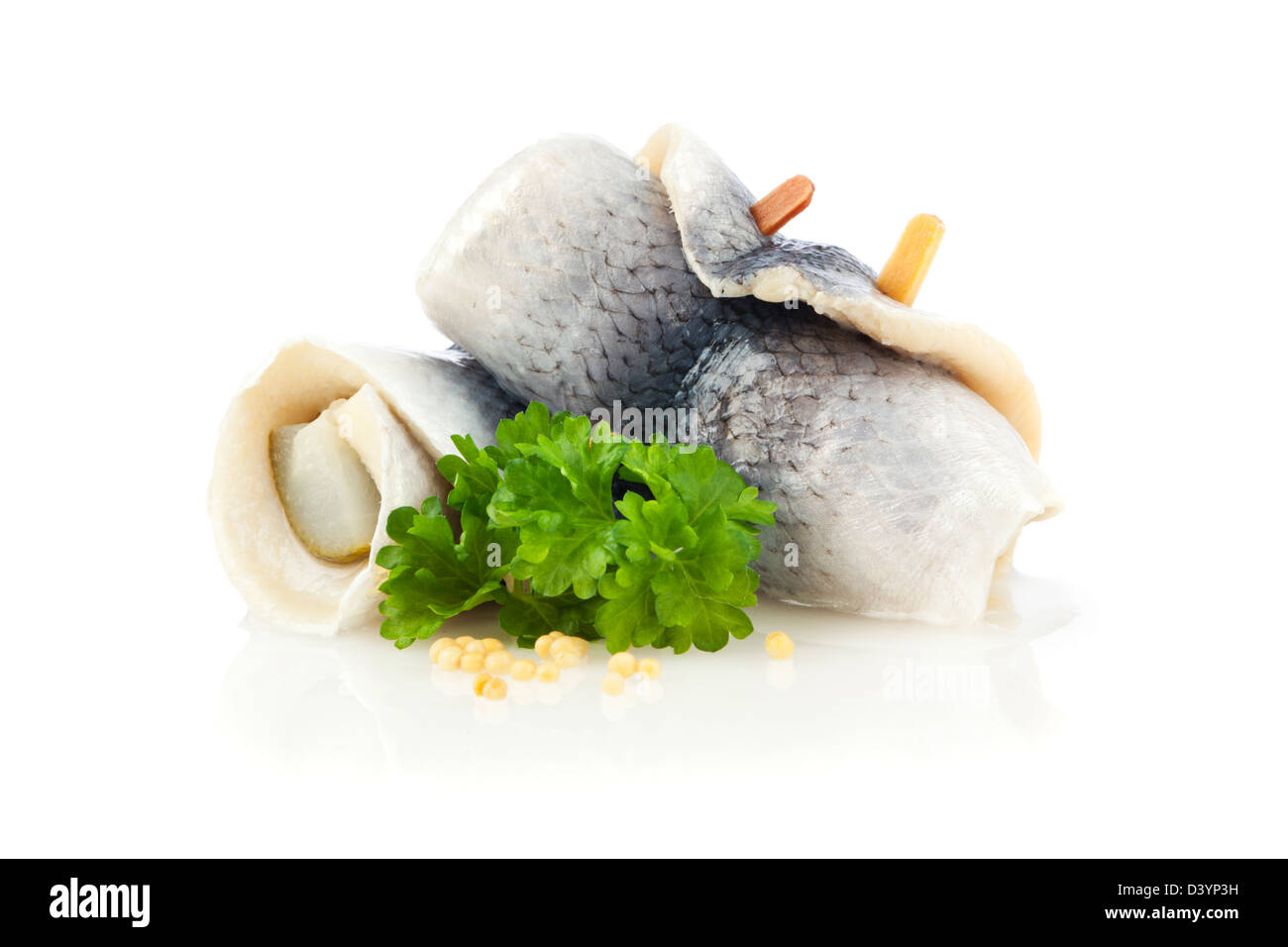 German Rollmops - kipper wrapped around pickled cucumber, garnished with parsley and mustard seeds, on white background - Stock Image