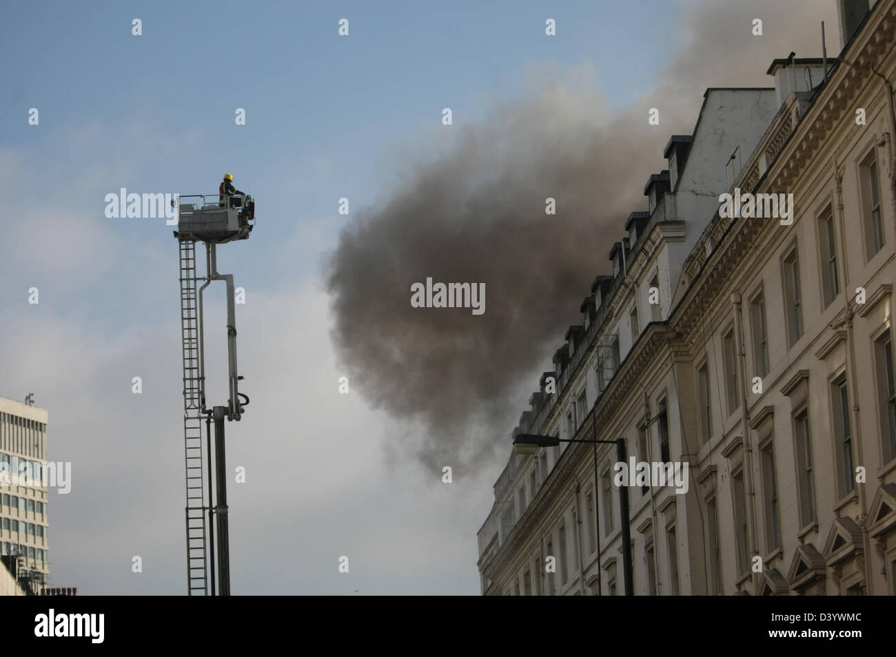 London, UK, 27 February 2013, Smoke billows from the roof as firefighters tackle blaze in Bayswater. Station Manager - Stock Image