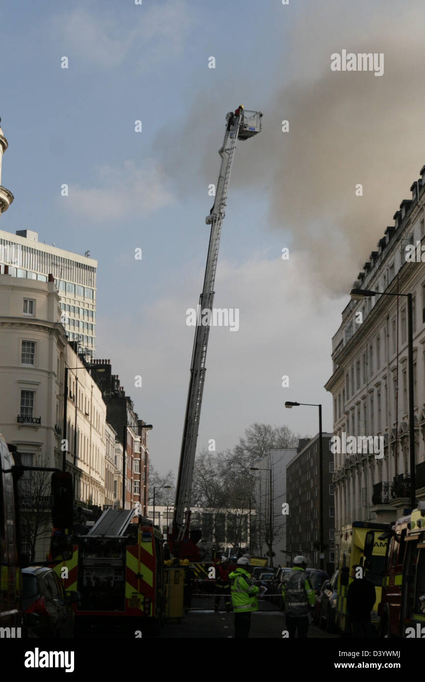 London, UK, 27 February 2013, Firefighters aim hoses at blaze in Bayswater hotel. Station Manager Nick Comery, who - Stock Image