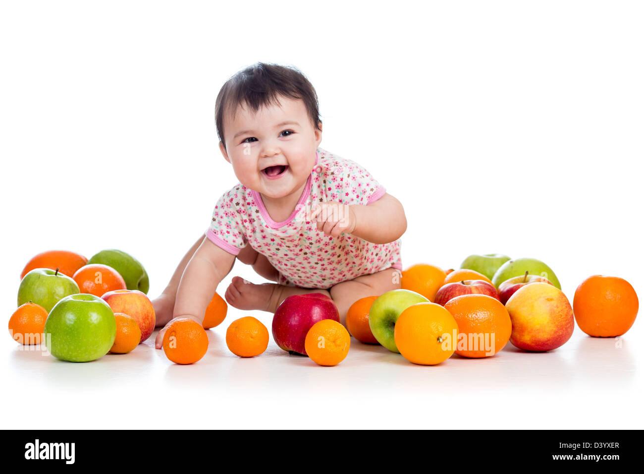 happy baby girl sitting among fresh fruits - Stock Image