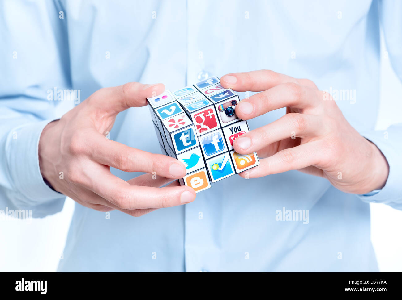 Businessman solving rubik's cube with logotypes of well-known social media brand's. Stock Photo