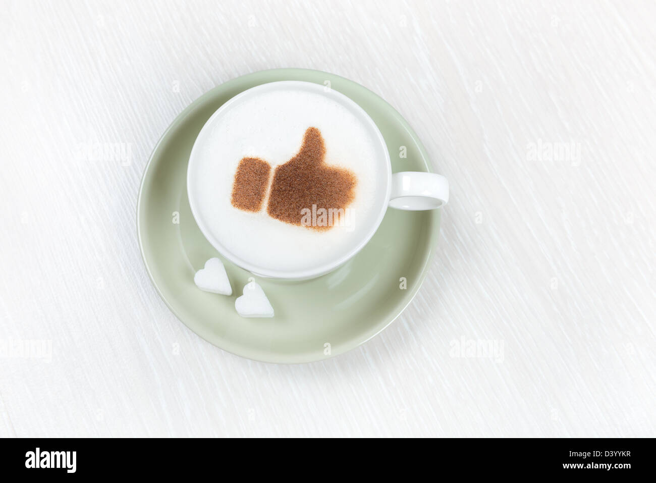 Cup of coffee with chocolate thumbs up and heart shaped sugar - Stock Image