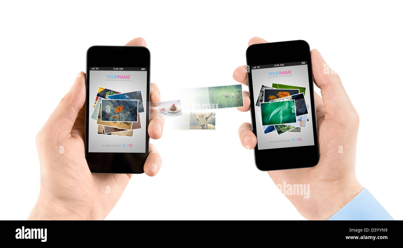 Two hands holding mobile smartphones while transferring pictures from one to another. - Stock Image