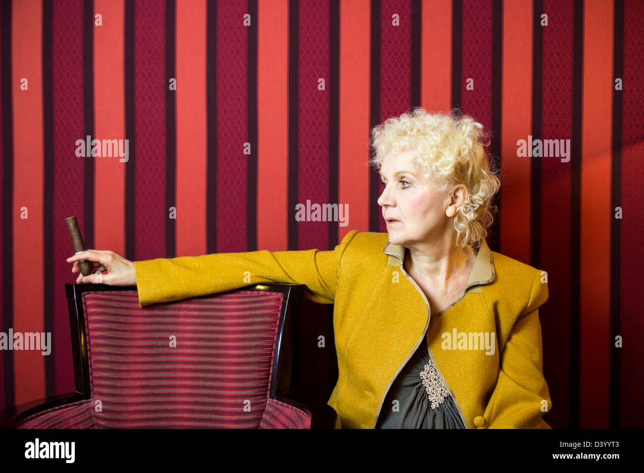 Blond senior woman sitting and holding and looking her cigar - Stock Image