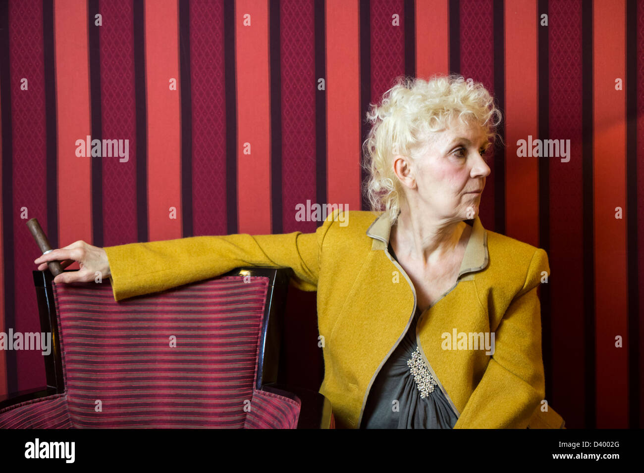 Blond senior woman sitting and holding a cigar - Stock Image