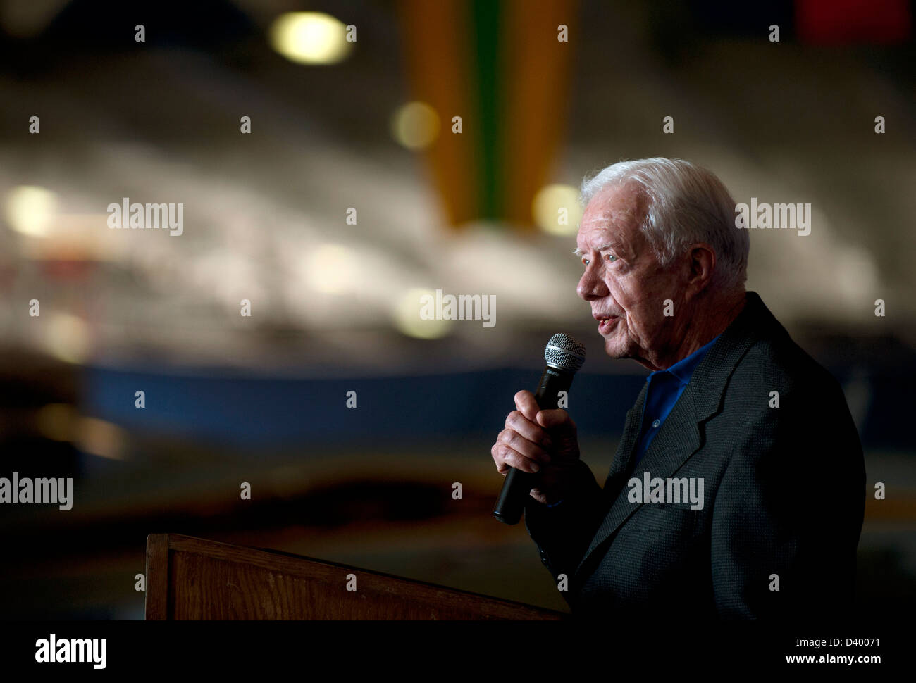 Former President Jimmy Carter addresses Sailors and guests in the hangar bay during a visit to the aircraft carrier - Stock Image
