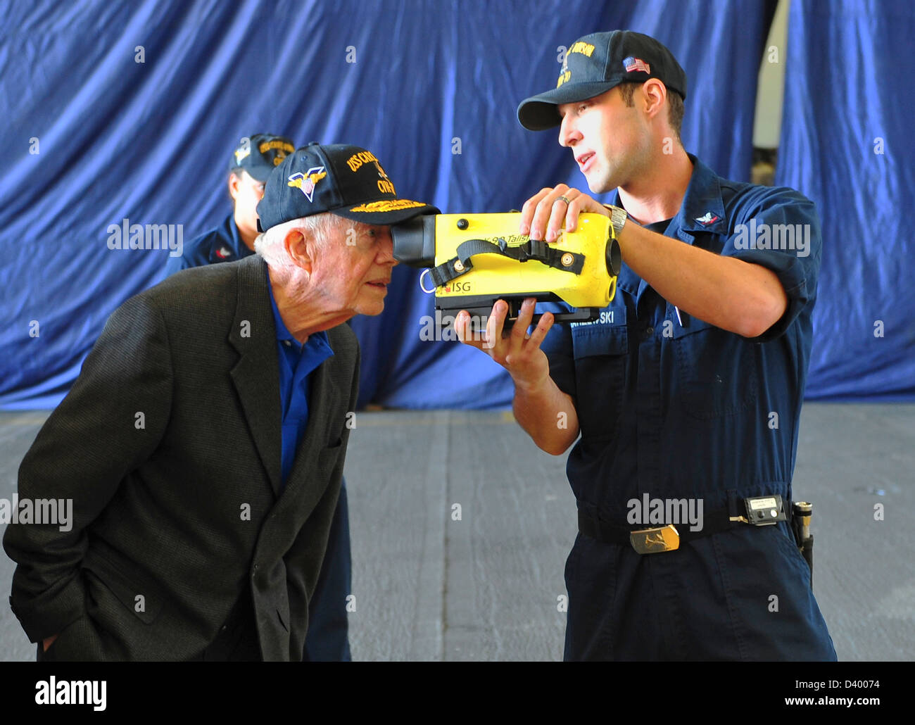 Former President Jimmy Carter is shown a naval firefighting thermal imager by a sailor during a visit to the aircraft - Stock Image