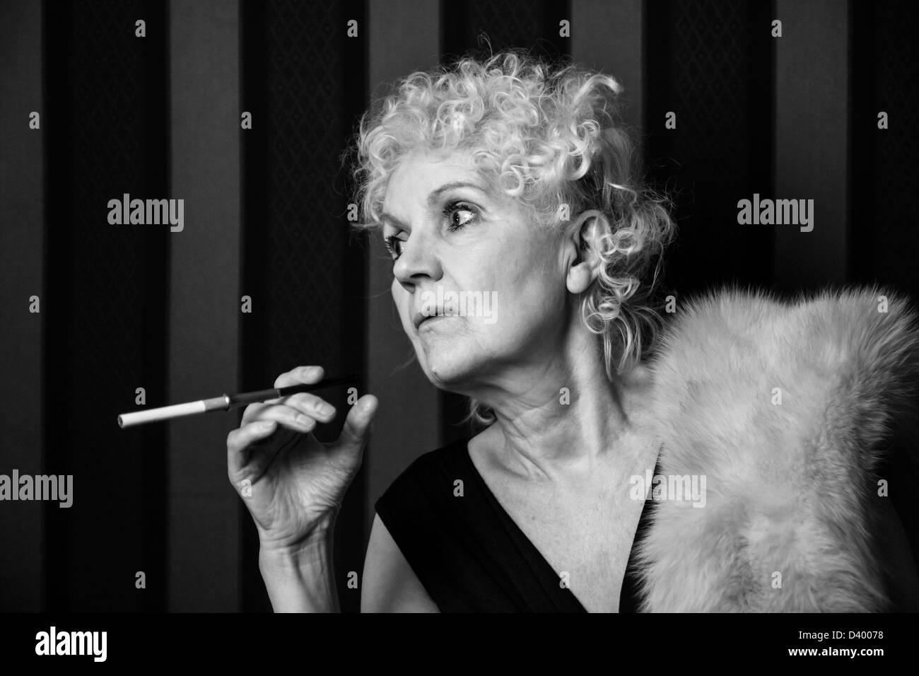 Bond senior woman holding a cigarette holder - Stock Image